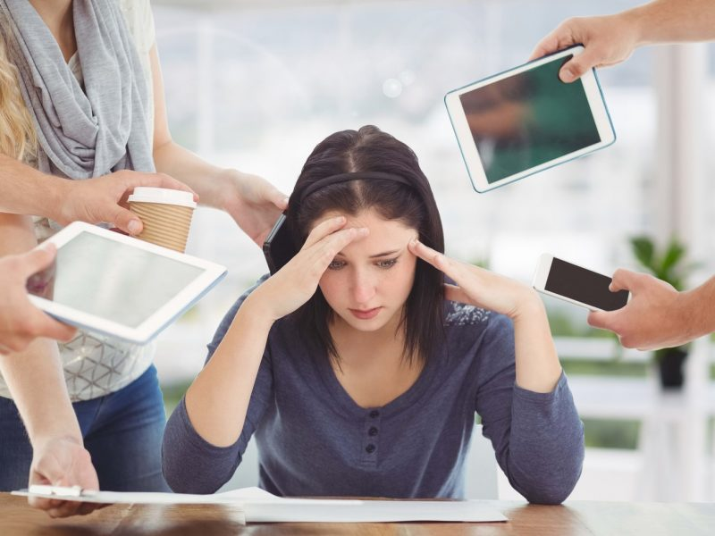 Conceptual image of stressed woman with electronic devices at office
